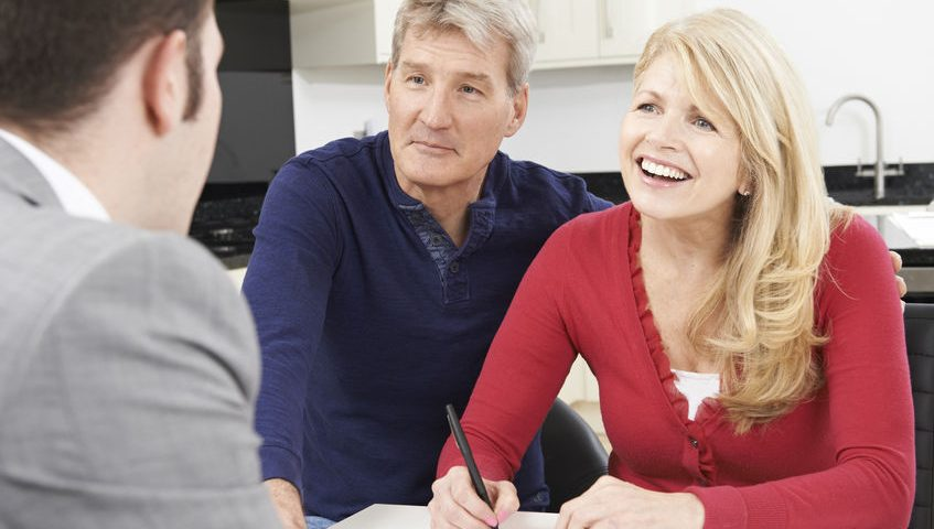 44085356 - mature couple with financial advisor signing document at home