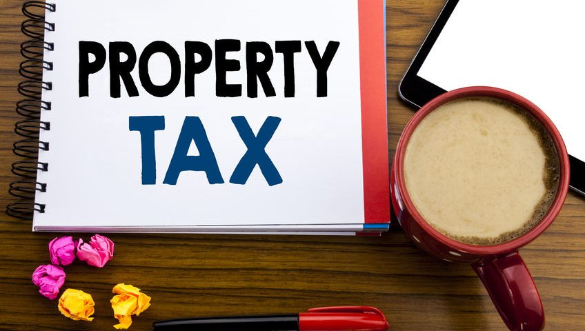 96636739 - handwritten text showing property tax. business concept writing estate income taxation written on notepad paper, old black wooden background in office view with pen coffee and tablet