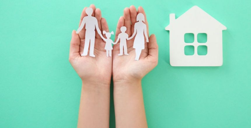 Woman holding paper family cutout near house model on color background, top view